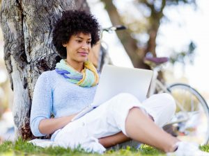 Woman working outdoors in a meadow with laptop